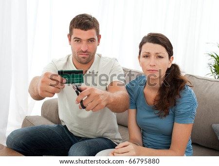 Worried couple cutting their credit card together sitting on the sofa at home - stock photo