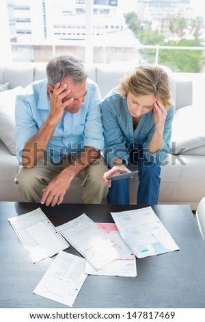 Worried couple sitting on their couch paying their bills at home in the living room - stock photo