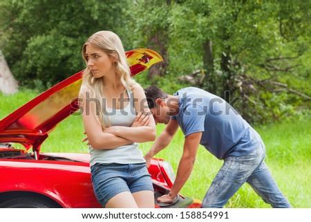 Worried couple waiting for assistance after breaking down with their car - stock photo