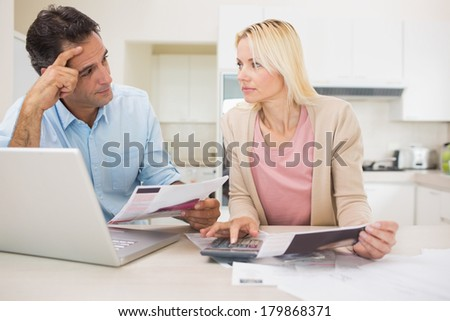 Worried couple with bills and laptop in the kitchen at home - stock photo