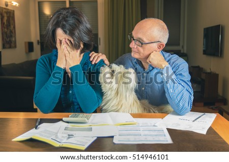 Worried couple with dog reading an important notification in a letter sitting in the living room at home