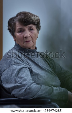 Worried despair senior woman sitting in a wheelchair - stock photo