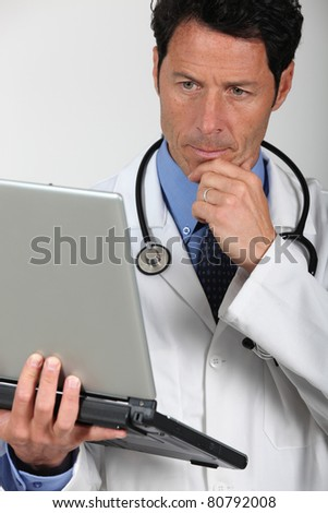 Worried doctor looking at laptop - stock photo