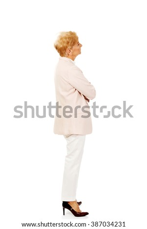 Worried elderly business woman with arms folded - stock photo