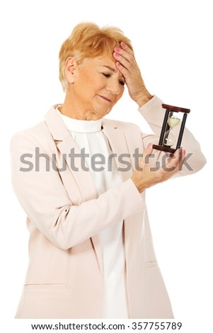 Worried elderly business woman with palm on her forehead holding hourglass. - stock photo