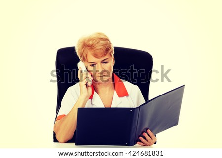 Worried elderly female doctor or nurse sitting behind the desk and talking through a phone