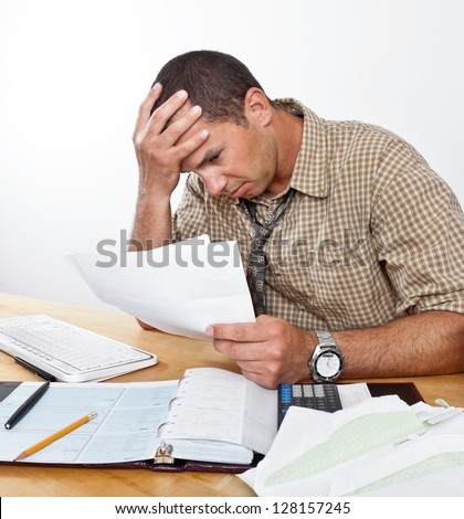 Worried exhausted young man sits at desk paying bills, head in hands.
