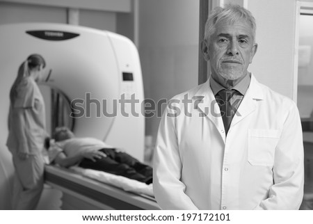Worried expert senior male doctor awaiting his patient to undergo a CT scan, with her assistant helping in background. - stock photo