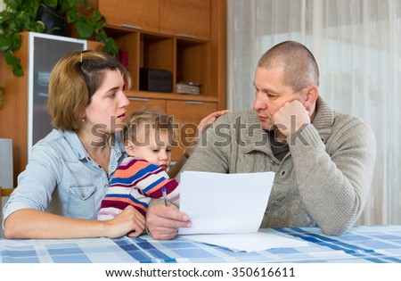 Worried family with child sitting with financial documents at home - stock photo