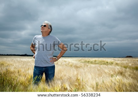Worried farmer  scrutinizing a threatening cloudy sky. - stock photo
