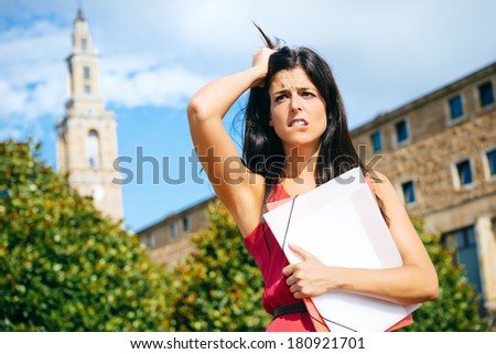 Worried female student in problems. Stressed young woman at university campus after educational fail. - stock photo