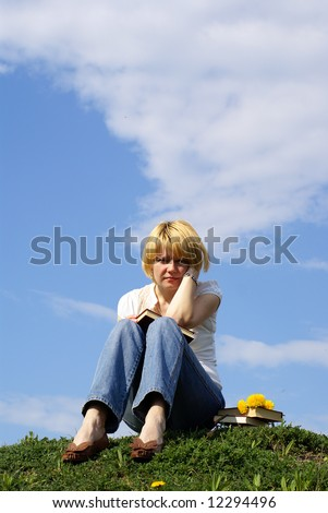 worried  female student with books on green grass  and blue sky on background - stock photo