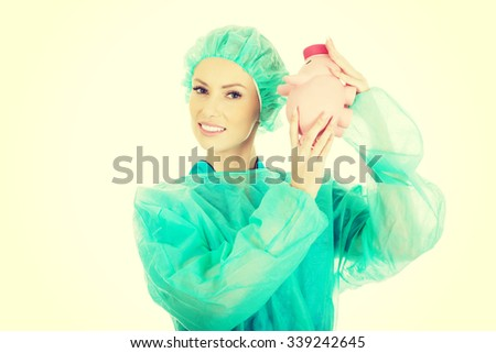 Worried female surgeon doctor with piggy bank. - stock photo