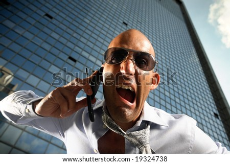 Worried, frustrated, freaked-out business man yelling at a cell phone on a business building background. - stock photo