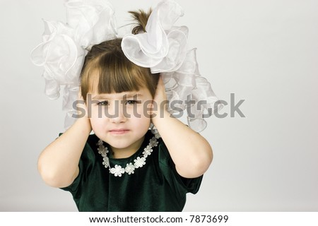 Worried girl with huge bows dressed for holiday - stock photo
