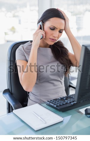 Worried gorgeous businesswoman having a phone call in her office - stock photo