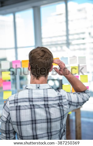 Worried hipster man in front of post-it in office - stock photo