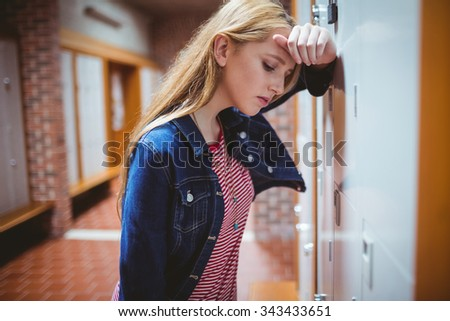 Worried leaning against the locker at the university - stock photo