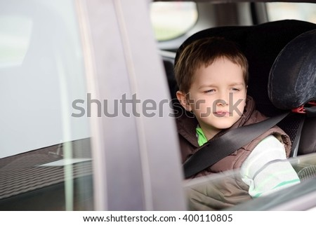 Worried little boy in car safety seat. Looking through the window. Children car safety concept.  - stock photo