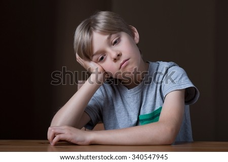 Worried little child sitting at the desk - stock photo