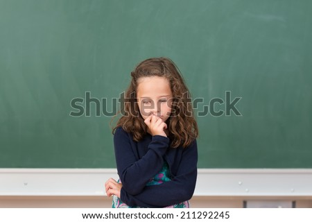 Worried little girl in school sitting at her desk in front of the blank blackboard staring morosely down at her class notes - stock photo