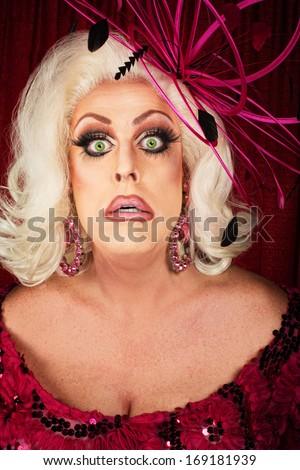 Worried man dressed as blond female singer - stock photo