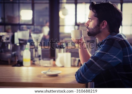 Worried man drinking a coffee at the cafe - stock photo