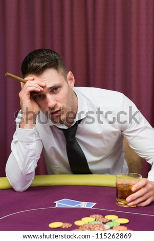 Worried man holding a cigar at poke at table in casino