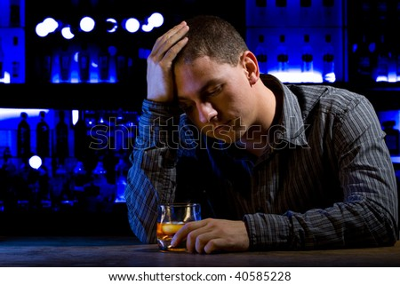 Worried man sitting at bar with whiskey glass. Dark night scene. Blue background - stock photo