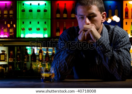 Worried man sitting at bar with whiskey glass. Dark night scene. Colored background - stock photo