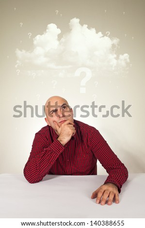 Worried man sitting at the table with hand on his chin; cloud of questions above his head.
