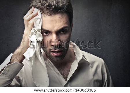 worried man wipes sweat on his face - stock photo