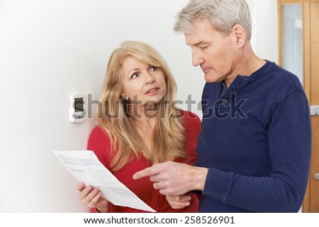 Worried Mature Couple With Bill Turning Down Central Heating - stock photo