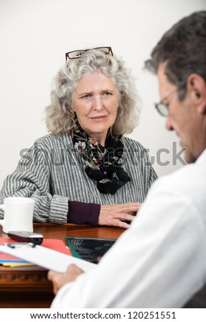 Worried mature woman patient listens to doctor in his office. Focus on woman. - stock photo