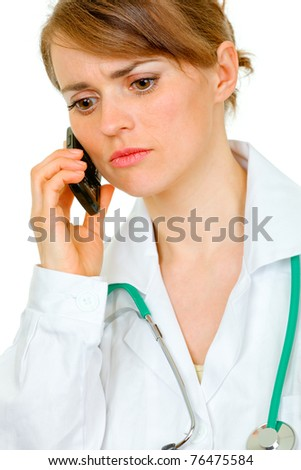 Worried medical female doctor talking on mobile phone isolated on white - stock photo