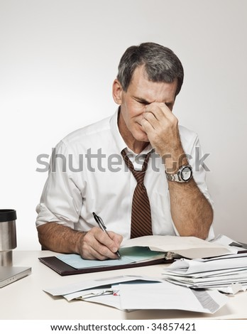 Worried, middle age man rubbing his forehead in pain, paying bills and writing checks - stock photo