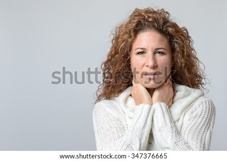Worried middle aged woman looking at the camera with her hand raised to her neck and a pained serious expression, over grey with copyspace - stock photo
