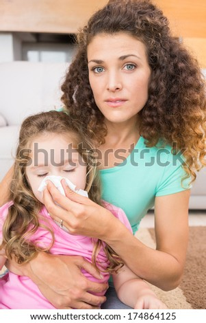 Worried mother helping her little daughter blow her nose at home in living room - stock photo