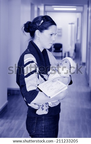 Worried mother holds her sick baby in hospital ward corridor. Concept photo of childhood , health care, medical treatment  and motherhood. - stock photo