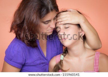 Worried mother taking the temperature of her sick and exhausted daughter