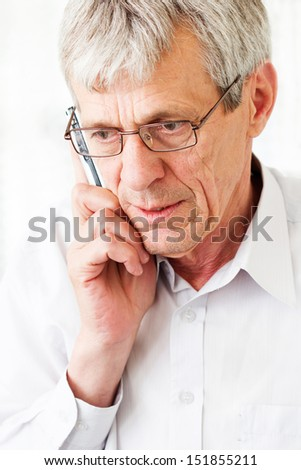 Worried older man talking on phone - stock photo