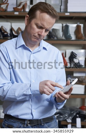 Worried Owner Of Shoe Store With Calculator - stock photo