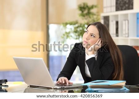 Worried pensive businesswoman looking sideways in a desktop at office - stock photo