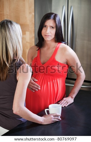 Worried pregnant woman holds her tummy with friend in kitchen - stock photo