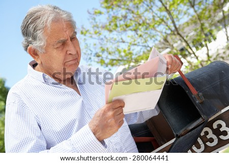 Worried Senior Hispanic Man Checking Mailbox - stock photo