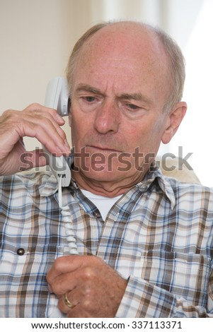 Worried Senior Man Answering Telephone At Home - stock photo