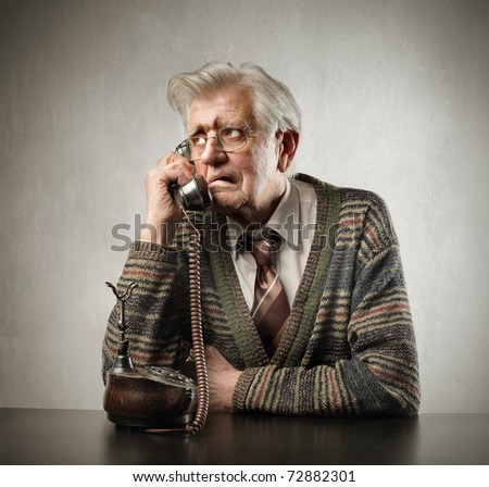 Worried senior man talking to telephone - stock photo