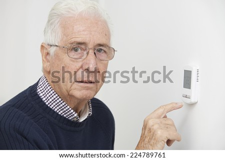 Worried Senior Man Turning Down Central Heating Thermostat - stock photo