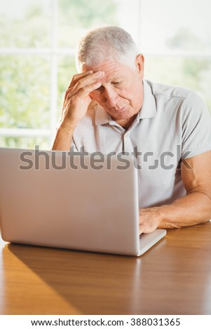 Worried senior man using laptop at home