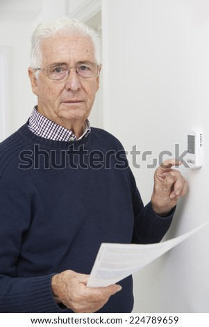 Worried Senior Man With Bill Turning Down Central Heating Thermostat - stock photo